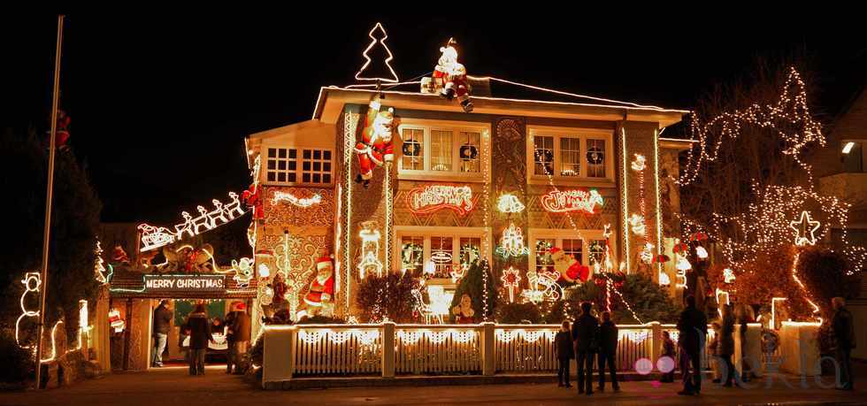 People walking in front of a seasonaly decorated house in the Niendorf district of Hamburg, northern Germany, admire the colorful Christmas illumination on Saturday evening, Nov. 28, 2009.